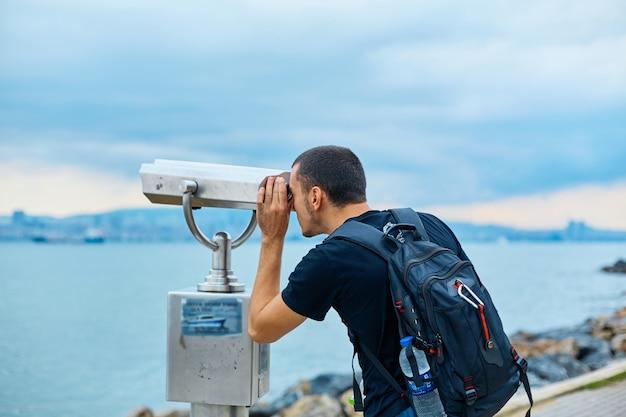バックパックを背負った観光客が展望台の観光双眼鏡で覗く
