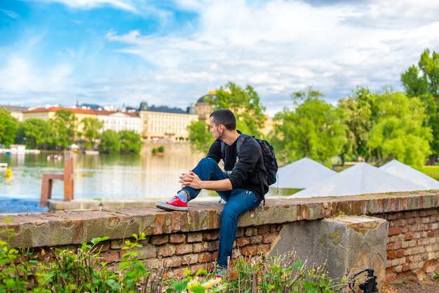Парень-турист с рюкзаком сидит на набережной в праге с видом на реку влтава.