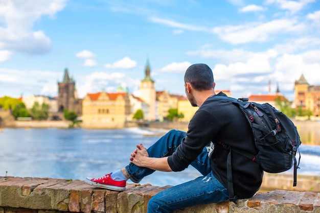 Турист с рюкзаком сидит на набережной в праге с видом на реку влтава.