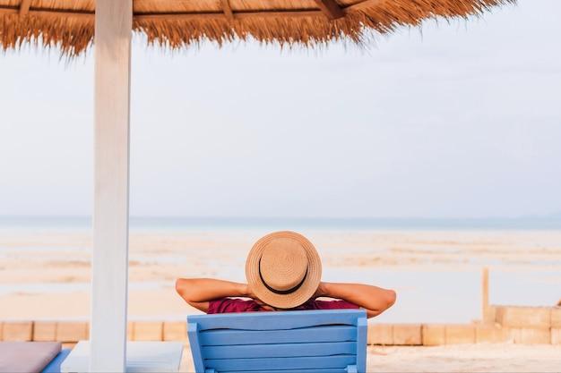 Туристический человек отдыхает на шезлонге на берегу моря летом на фоне голубого неба. концепция счастливого путешествия в выходные.