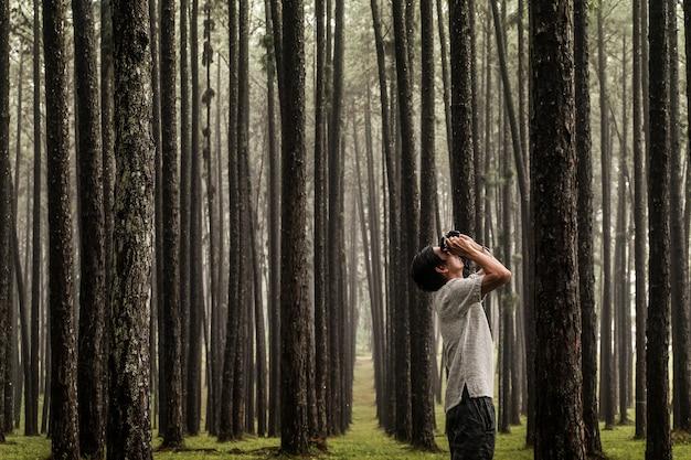Туристический человек сфотографироваться в сосновом лесу