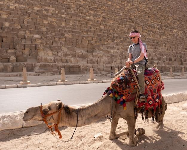 ラクダの観光客がギザのピラミッドを背景にポーズをとる