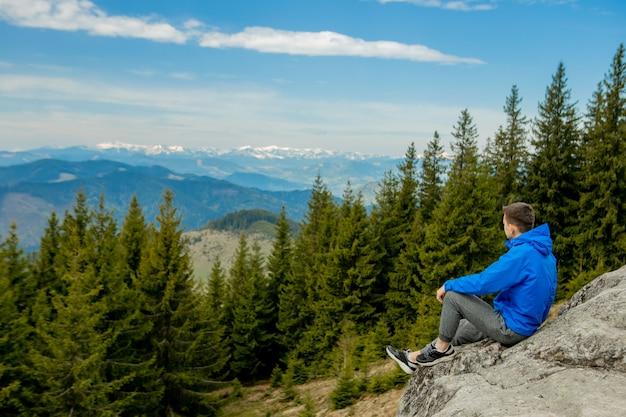 崖の上に座って遠くを見ている観光客