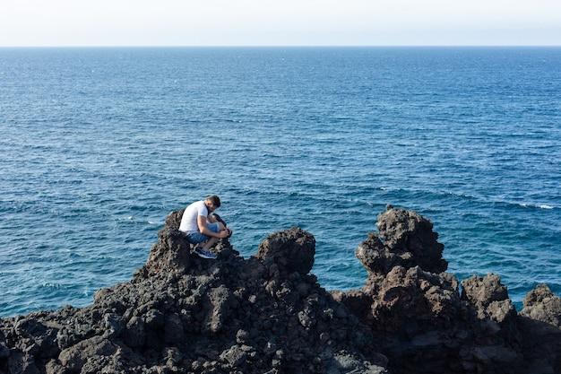 관광객은 배경 푸른 바다에 바위에 쪼 그리고 앉는 사진을 걸립니다. 스페인 란사로테 섬.