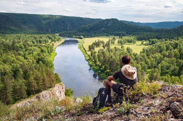 Турист с рюкзаком и камерой на скале, наслаждаясь видом на долину реки