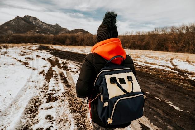 배낭을 든 관광객이 산을 올라갑니다. 자연의 배경에 뒤를 가진 여행자의 사진.