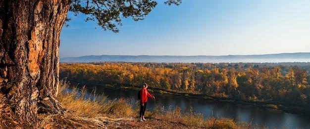 Турист с рюкзаком стоит на холме и смотрит на реку