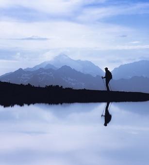 バックパックを持った観光客が水の反射で山の湖に沿って歩く