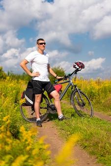 夏の緑の芝生を背景に自転車を持った観光客が立つ