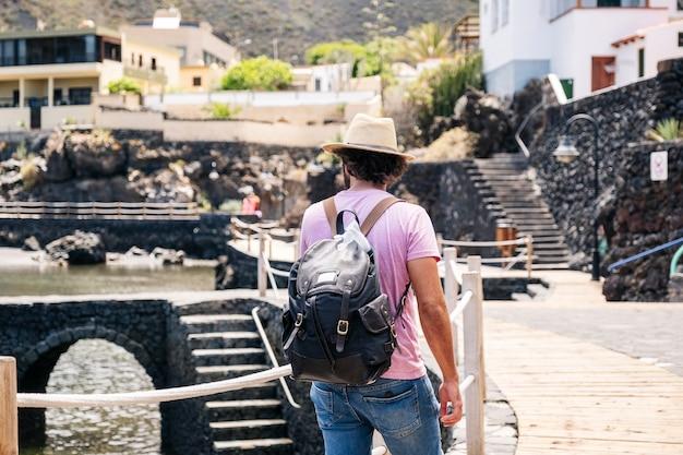 Турист с шляпой и рюкзаком в прибрежном городке эль йерро, канарские острова