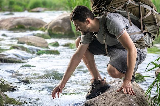 Турист с большим походным рюкзаком охлаждается в летнюю жару у горной реки.