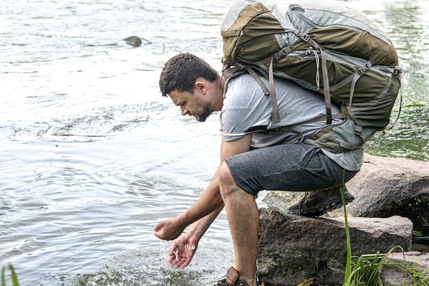 Турист с большим походным рюкзаком у горной реки в летнюю жару.