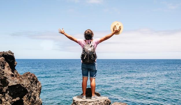 Турист с шляпой и рюкзаком на побережье с морем на заднем плане.