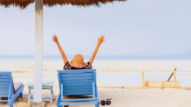 Туристическая женщина отдыхает на шезлонге на берегу моря летом на фоне голубого неба. концепция счастливого путешествия в выходные.