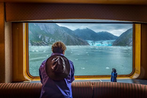 旅行の背景のための大きなクルーズ船の窓を探して観光の女性