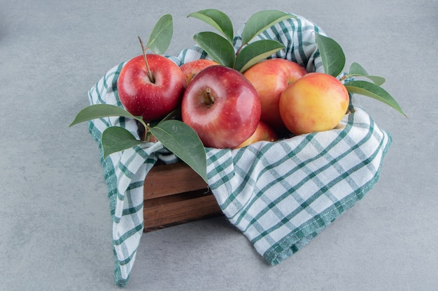 タオルで覆われた木枠と大理石のリンゴの束