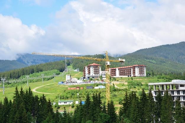 Башенный кран летом строит горнолыжный курорт в горах, на фоне гор, лесов и строящихся отелей. видны подъемники и голубое небо