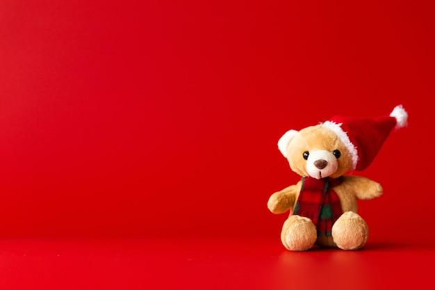 На красном фоне сидит игрушечный медведь в красной шапке и шарфе. горизонтальное фото