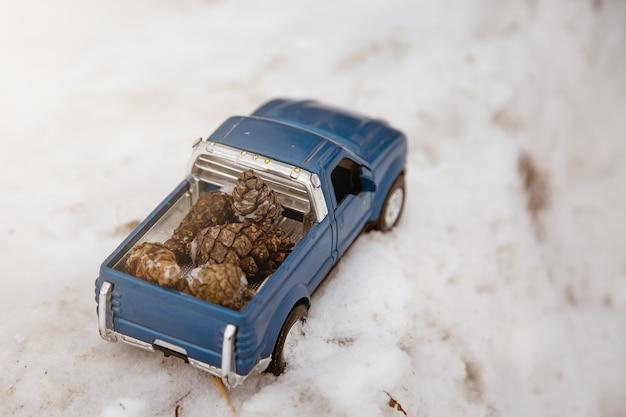 도로의 겨울 숲에 있는 장난감 파란색 픽업 트럭 차체 뒤쪽에 전나무 콘을 싣고