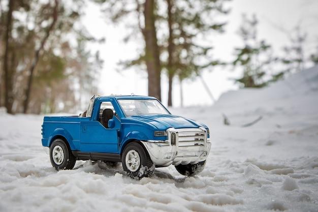 열린 문으로 서 있는 도로의 겨울 숲에 있는 장난감 파란색 픽업 트럭
