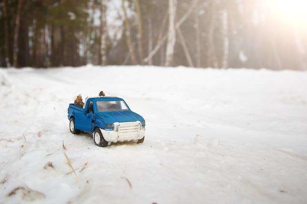 도로에 문이 열려 있는 겨울 숲의 장난감 파란색 픽업 트럭