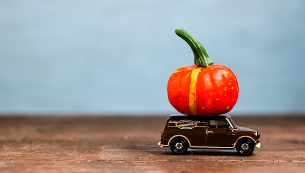Игрушечная машинка с большой оранжевой тыквой концепция осеннего сбора урожая