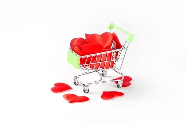 Игрушечная тележка из супермаркета, наполненная красными сердечками на белом, концепция любви и дня святого валентина.