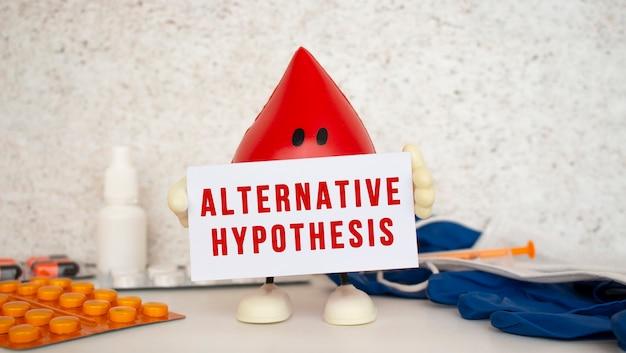 おもちゃの血の滴は、対立仮説の碑文が書かれたホワイトペーパーカードを保持しています