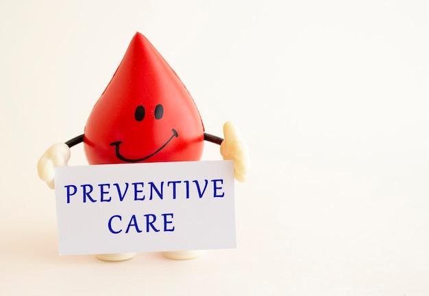 おもちゃの血の滴は、予防ケアの碑文が書かれた白い紙のカードを保持しています
