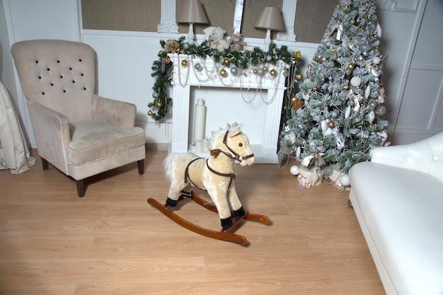 おもちゃの馬は、装飾された輝くクリスマスツリーとアームチェアの近くに立っています。