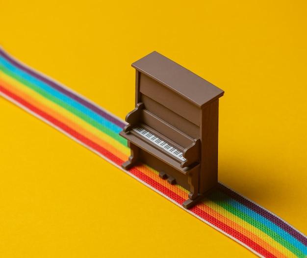무지개 색 스트립에 장난감 피아노가 서 있습니다.