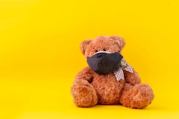 保護フェイスマスク、コロナウイルスの流行の概念を持つおもちゃのテディベア Premium写真