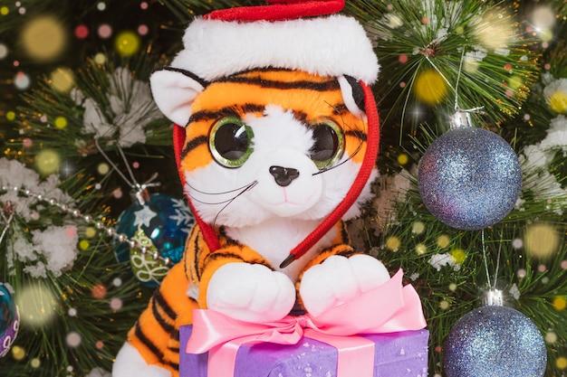 조명이 있는 크리스마스 트리 배경에 모자를 쓴 장난감 호랑이.