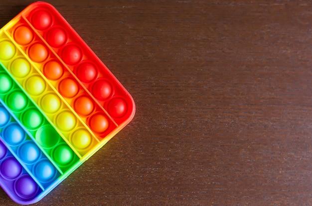 シリコーンの質感の背景を持つおもちゃ。虹色の色。フィジェットプッシュポップは、抗ストレス感覚のおもちゃです。