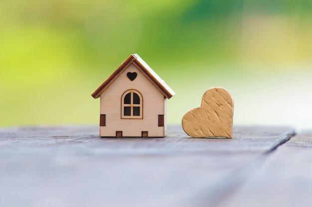 木製のテーブルにゴールドのハートの横に立っているおもちゃの木造住宅