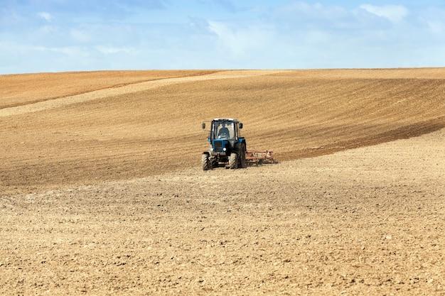 Трактор вспахивает поле, находящееся в земле во время посева.