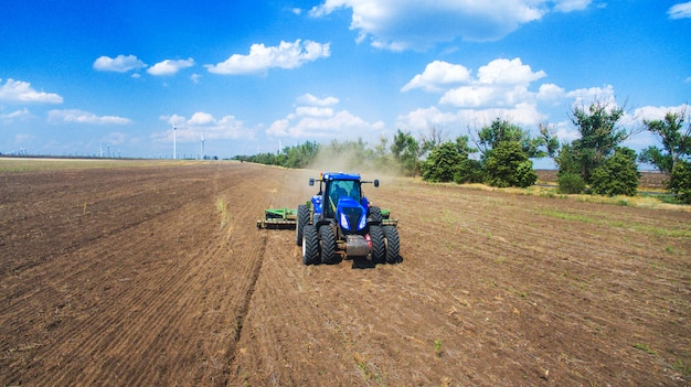 Трактор пашет и сев в поле