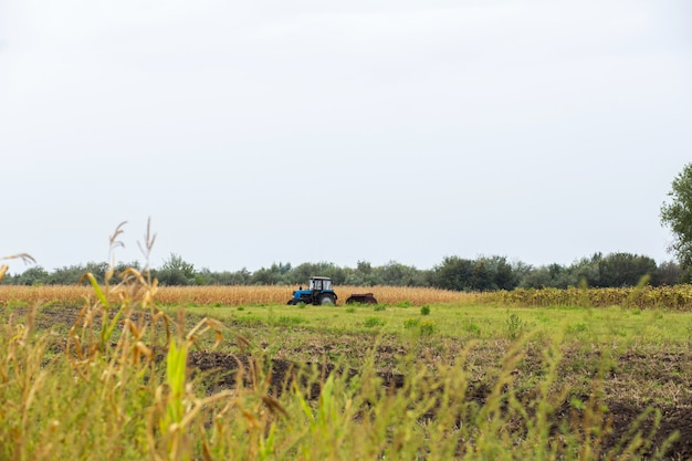 Трактор пашет поле с плугом. сельский пейзаж аграрной страны. соу сезон
