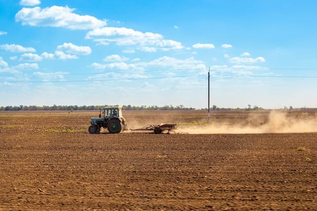 トラクターが農作物のために肥沃な土地を耕す