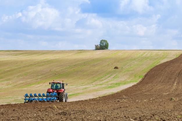 큰 쟁기를 가진 트랙터는 밭을 쟁기질합니다. 농업 첨부 파일이있는 트랙터. 파종을위한 토지 준비.