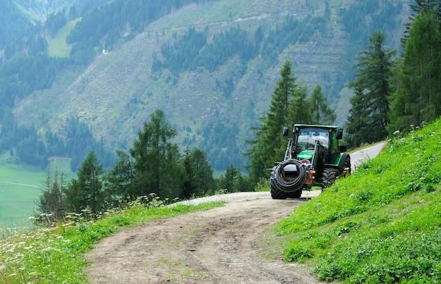 오스트리아 알프스 산맥의 높은 들판에서 일하는 트랙터
