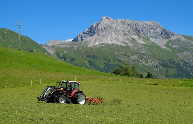 높은 산의 들판에서 일하는 트랙터