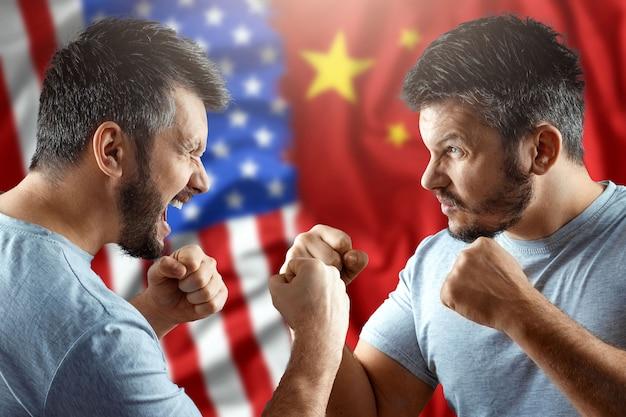 В торговой войне между китаем и сша двое мужчин готовятся к бою на фоне американского и китайского флага. перемирие, война, санкции, бизнес.