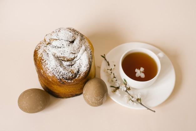 Традиционный пасхальный кулич, посыпанный сахарной пудрой, цветными бежевыми яйцами и чашкой черного чая в белой кружке и веточкой цветущей яблони. праздничная открытка