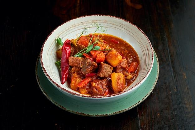전통적인 헝가리 요리는 bograch 또는 감자와 돼지 고기가 들어간 두꺼운 고기 빨간색 굴 라시 수프로 어두운 배경에 흰색 그릇에 담겨 제공됩니다.