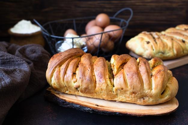 Kulebyaka라는 러시아 요리의 전통적인 짭짤한 파이. 반죽 버터, 밀가루, 계란 재료. 고기와 양배추 파이. 어두운 소박한 배경입니다. 확대