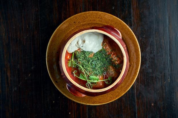 Традиционное украинское блюдо - голубцы с фаршем и рисом в миске с красным соусом и сметаной.