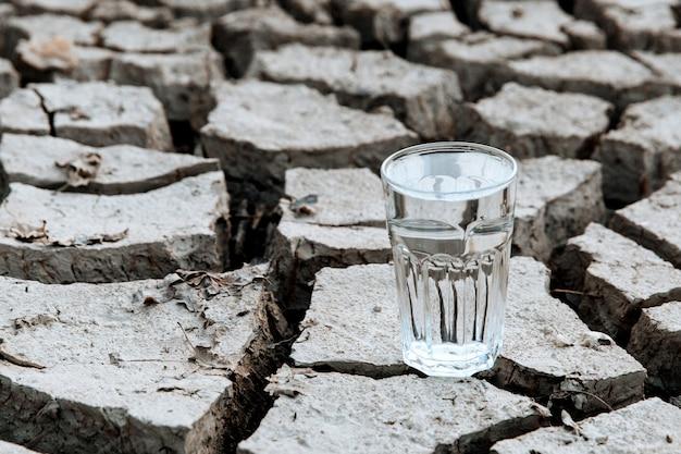 Прозрачный стакан чистой питьевой воды стоит посреди сухой потрескавшейся пустынной земли. концепция глобального потепления. засуха и водный кризис