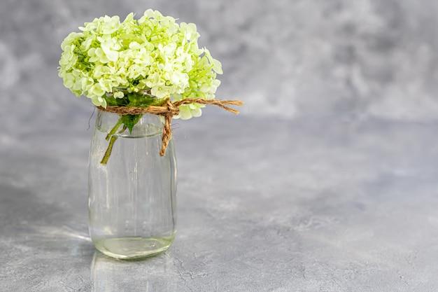 灰色の背景に新鮮な切り花がいっぱい入った透明な花瓶 Premium写真