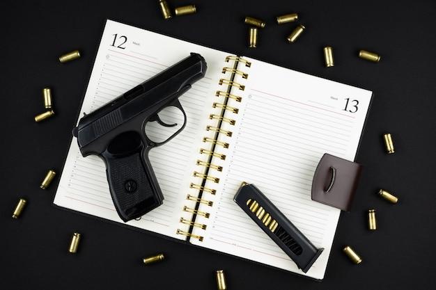 외상성 권총과 탄약이 검은 색 표면에 열린 노트북에 누워 있습니다.